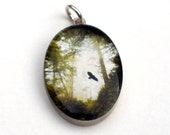 Crow Pendant -  A Solitary Crow Soars in the Woods in Sterling Silver and Resin Oval Pendant with Fine Art Image Transfer