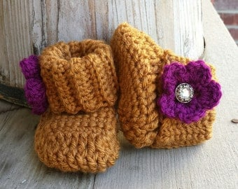 Crochet baby girl boots, in honey with plum flower and pearl button center. size 0 to 3 mo.