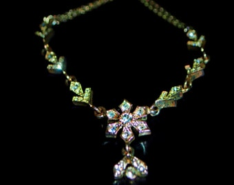 Classy vintage 80s silvertone metal necklace with snowflake as a centerpiece, accented with marquisite and clear rhinestones. Napier.