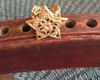 A star ring made from brass filligree.