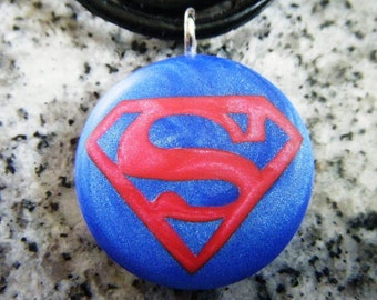 Super Hero hand carved on a Polymer clay blue pearl color background. Pendant comes with a FREE necklace