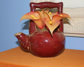 Brown teapot filled with calla lilies