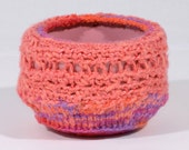 Fiber Art Bowl cover - silk and cotton- crocheted and knit with mixed color yarns, wrapped around a pink bowl