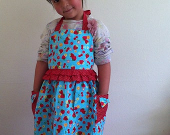 Girl's apron, red strawberry pattern on a blue fabric.