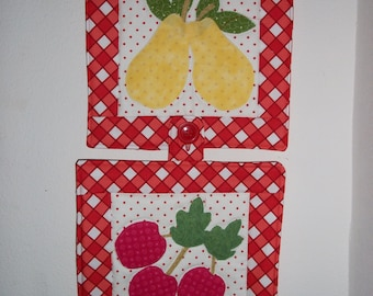 Pair of red check pot holders and wall decor.