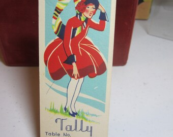 Art deco 1930's unused christmas winter theme bridge tally girl caught in a wind storm with matching red dress hat and multicolored scarf