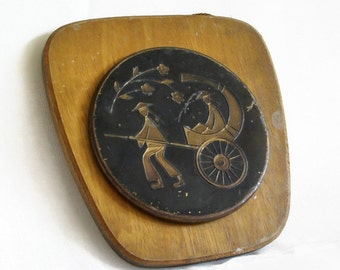 Asian pull rickshaw cart . Wall hanging, embossed round metal picture on wood Vintage brass. Home decor, Two wheeled Ricksha wooden carriage