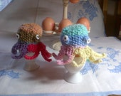 A pair of hand knitted striped octopus egg cosies