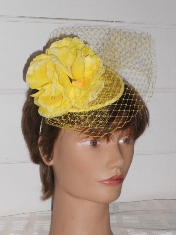 Yellow floral headpiece on a sinamay base.