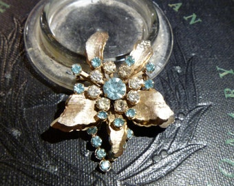 Lovely flower brooch with light blue and clear rhinestones.