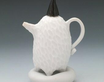 Carved white porcelain teapot on pillow