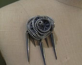 Grey zipper rosette brooch with spikes.