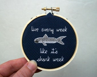 Live Every Week Like It's Shark Week cross stitch, completed in natural wood embroidery hoop