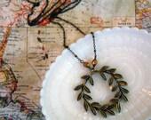 long antique brass laurel wreath necklace with matte gold tone czech glass bead accent