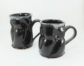 pair of black mugs sold together