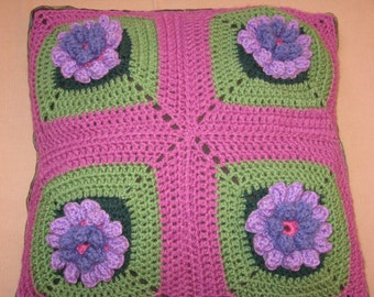 Crochet pillow cover with flowers in three dimensions within 4 granny squares