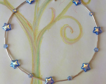 Glass star bead strung with strerling silver tube beads and a star toggle clasp