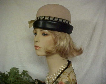 Union made beige cloche hat with side bow-leather band and a wrap around feather- fits 21 inches