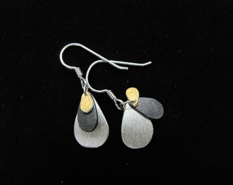 Tear drop silver earrings with overlapping black, gold, and silver segments