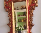 Italian wooden carved mirror with red paint and faux gold leaf accents.