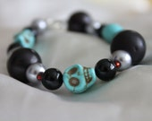 Black, Silver Beads with Teal Skull and Red Accented Bracelet