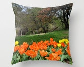 Spring flowers, orange tulips with a landscape of grass and trees.