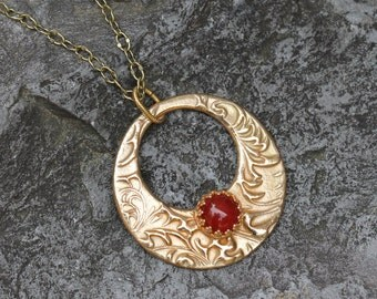 Carnelian and bronze round pendant necklace as gifted at GBK Gift Lounge for The Primetime Emmys