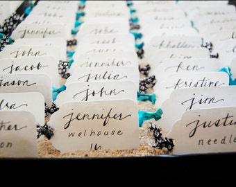 Paper tags with custom calligraphy names for seating cards, favors, personalized wedding party tags & gifts.