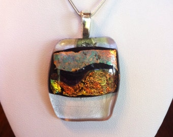 Dichroic glass pendant. Wave/design in shades of amber, with silver chain.