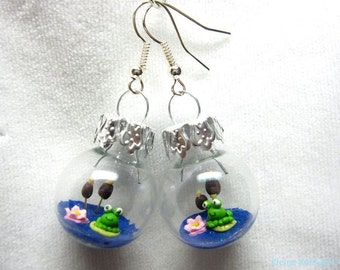 Frog in an earring, glas ball with frogs, lotus flower and reed
