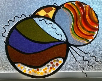 A lovely stained glass panel, contemporary and unique made  with a variety of techniques.  Is it an undersea creature?  From another planet?
