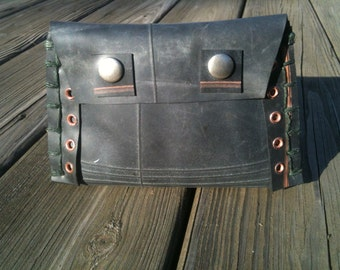 Rubber tire pouch with copper eyelets along seams and forest green stitching.