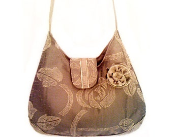 Beige embroidered bag with shiny gold piping