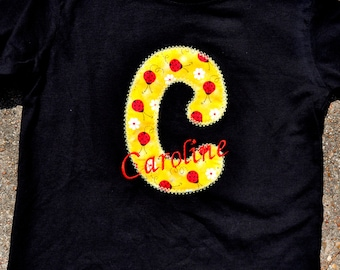 child's shirt or onesie monogrammed with large capital letter in choice of fabric and color and full name