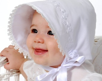 smiling baby wearing a bonnet