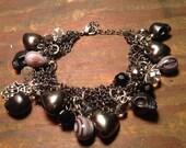 Bad-ass gunmetal rocker chick charm bracelet with black skulls, crystals, hearts, purple agate beads