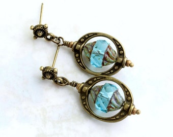 Turquoise Steampunk Earrings with compass rose earring posts, turbine beads surround by brass saturn rings, antique brass steampunk jewelry