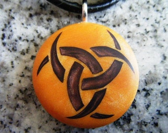 Triple Goddess hand carved on a polymer clay orange pearl color background. Pendant comes with a FREE 3mm necklace.