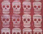 Sheet of red tissue paper handprinted with white skull lino print