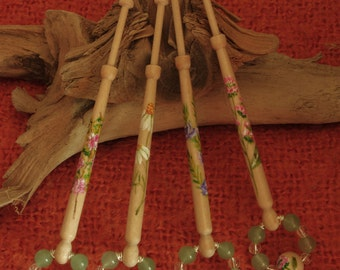 A set of four birch wood bobbins with a herb theme