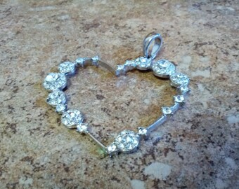 Beautiful heart shaped silver tone metal pendant with shiny crystals
