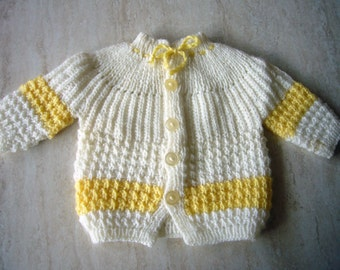 Baby handknitted cardigan with long sleeves and buttons in white and yellow.