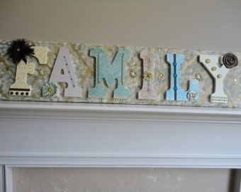 FAMILY letters decorated with scrapebook paper ribbon and jewels on a handpainted piece of wood