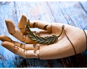 the phoenix feather necklace - large brass feather held captive by sumptuous brass chain