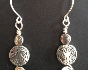 Swirl silver earrings with flower etched silver beads.
