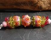 Handgemaakte glaskralen - Set van 9, 3 unieke ronde kralen in roze, geel en groen, 2 roze en 2 groene transparante bloemen en 2 spacers