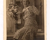 RPPC Woman Sitting in Window Holding Daisies in a Print Dress