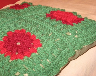 Crochet pillow cover with flowers in three dimensions within 4 granny squares in christmas colors