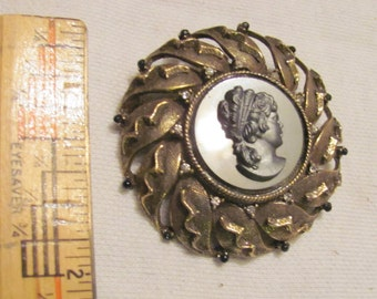 Cameo pin or pendant, black glass in gold metal with pewter face