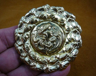 Woman with flowing hair and flowers on round leaf trimmed brass pin pendant  B-WOM-43